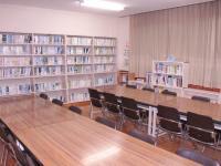 北公民館図書室の写真。奥に書棚があり、手前に長机が2つ並んでいる。