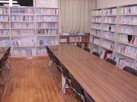 北公民館図書室の写真。部屋の壁に書棚があり、手前に長机が2つ並んでいる。