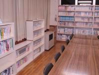 北公民館図書室の写真。部屋の壁沿いに書棚があり、手前に長机が1つある。