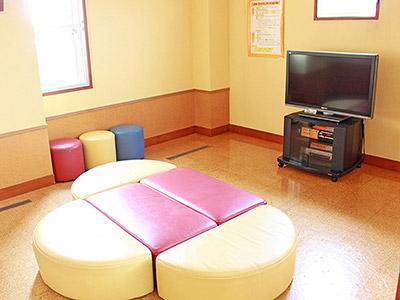 ミニシアターの写真。テレビがあり、テレビの前に椅子がある。